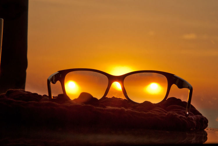 Close-up of sunglasses against sunset sky