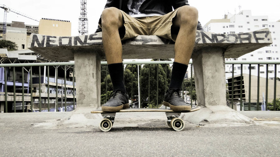 Low Section Of Man With Skateboard Sitting At Park