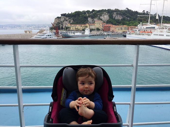 High angle view of baby boy looking away while sitting on stroller in boat
