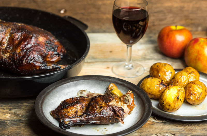 Goose baked with apples, wine and potatoes Goose Baked Apples Wineglass Preparation  Close-up Food And Drink Fried Potato Roasted Served Fried Baking Pan Potato Prepared Potato Roast Dinner