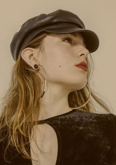 Close-up of young woman wearing cap against beige background