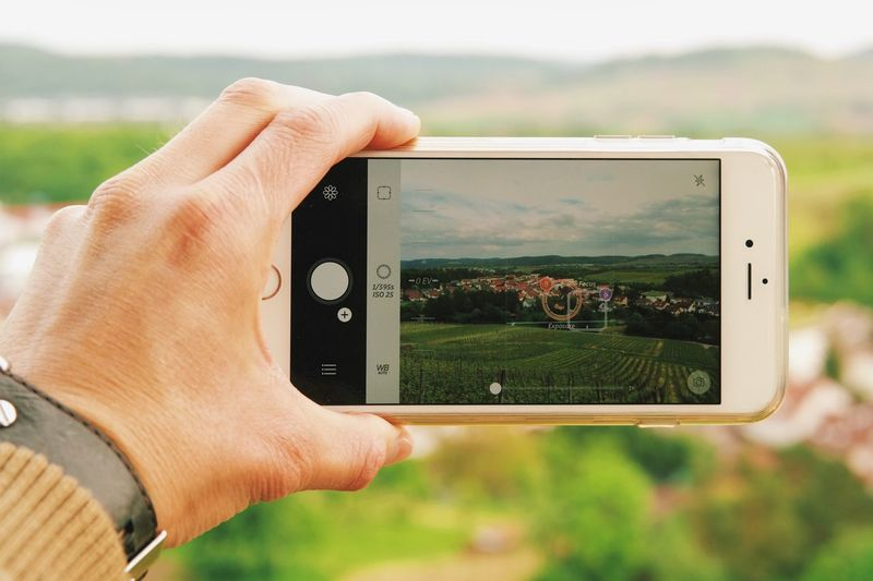 Cropped Image Of Man Photographing Landscape From Mobile Phone