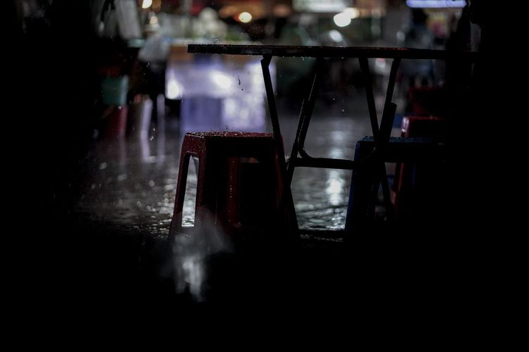 Empty chairs and table in cafe at night