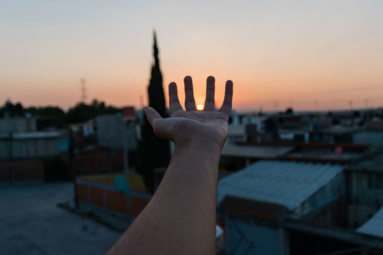 Cropped image of hand over city against sky during sunset
