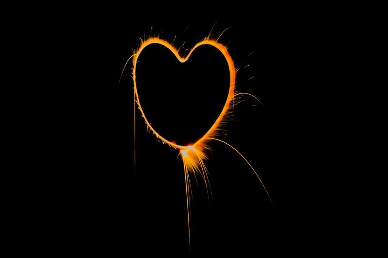 Close-up of heart shape light painting against black background