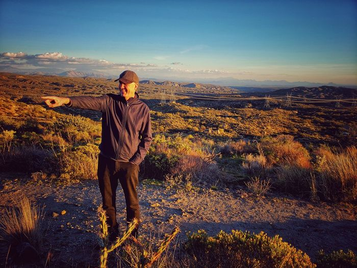 Man pointing on land against sky during sunset