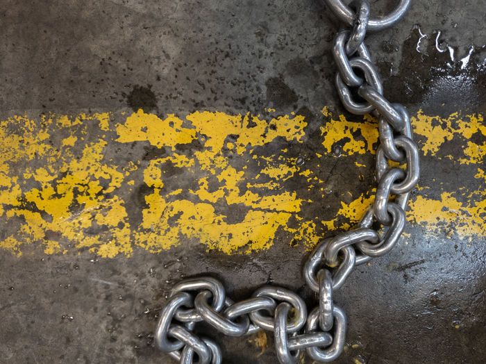 Close-up of metal chain against wall