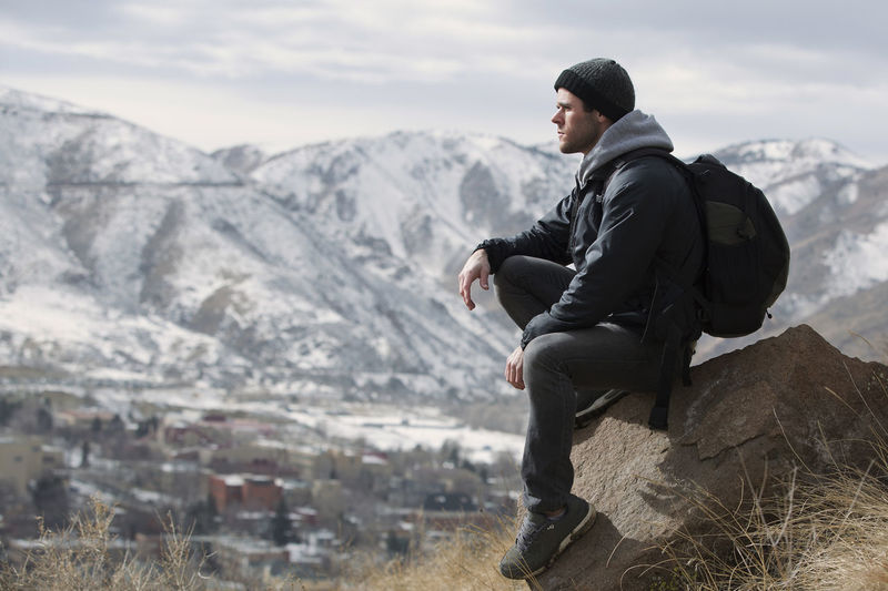 Relaxing in front of the glorious mountains. Colorado Mountains Snow Hiking Adventure Mountain Scenics - Nature Sitting Side View Young Men Rock Day Mountain Range Nature Rock - Object Leisure Activity Lifestyles Non-urban Scene Young Adult Beauty In Nature Men Outdoors Contemplation Looking At View Backpack