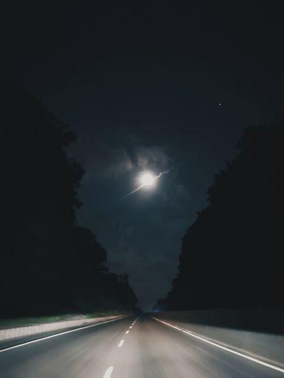 Road amidst illuminated street against sky at night