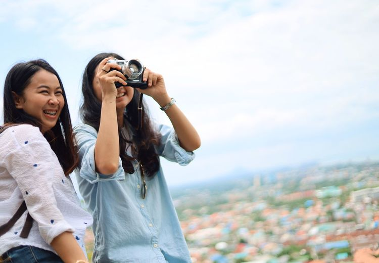Camera - Photographic Equipment Photography Themes Sky Technology Photographing Two People Togetherness Adult Casual Clothing Women Young Adult People Holding Real People Leisure Activity Young Women Nature Activity City Emotion Digital Camera Outdoors Positive Emotion Photographer Cityscape