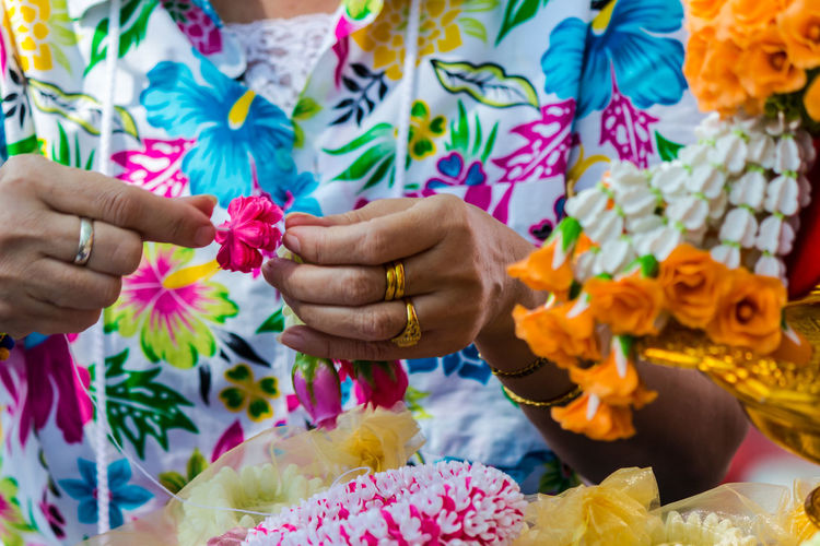 Midsection of woman making decoration with artificial flowers