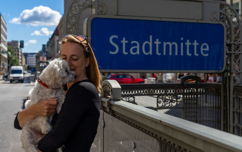 Woman standing with dog covered city