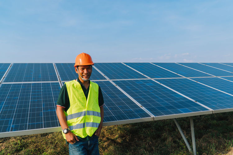 Portrait of engineer standing by solar panel