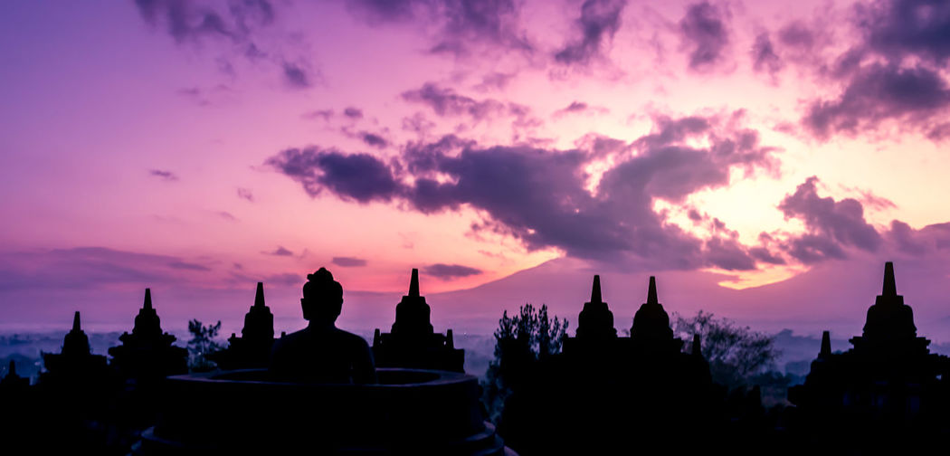 Silhouette buddha statue against sky during sunset