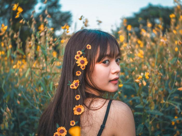 Portrait of woman wearing flowers amidst plants