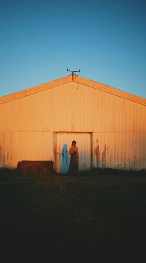 Rear view of woman standing by barn against clear blue sky