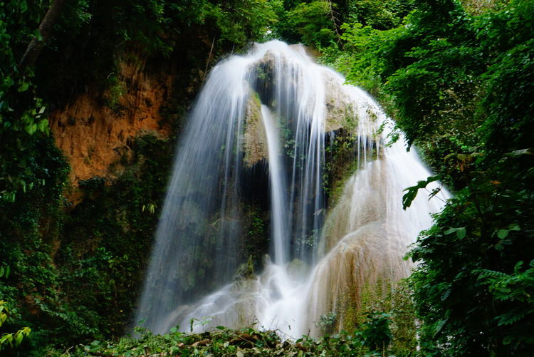 Tad Mok Waterfall. EyeEm Best Shots Beauty In Nature Blurred Motion Day Environment Falling Water Flowing Flowing Water Forest Growth Land Long Exposure Lush Foliage Motion Nature No People Outdoors Plant Power In Nature Rainforest Rock Scenics - Nature Tree Water Waterfall