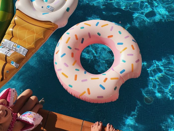 Multi Colored High Angle View Sweet Food Food Baked Table 10 Food And Drink Indulgence Day Human Body Part Sweet Birthday Lifestyles Human Hand Donut Shape Real People Still Life Celebration Floral Pattern