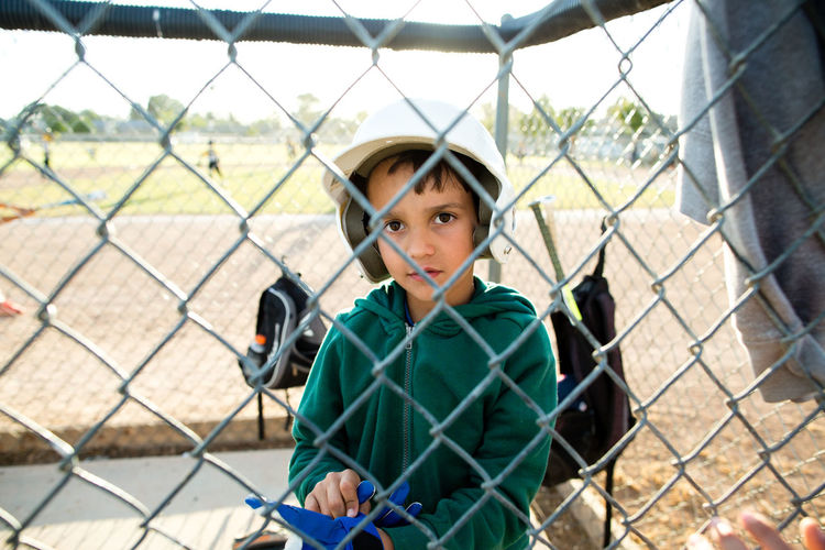 Portrait of boy looking through chainlink fence