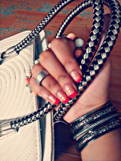 Cropped Image Of Hand With Nail Paint Holding Handbag