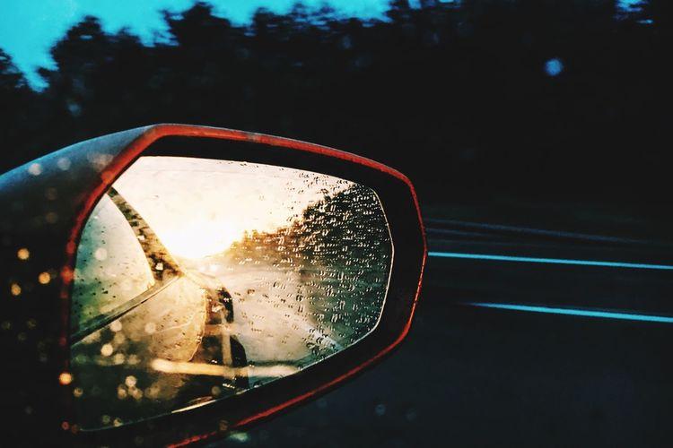 Side-view mirror of car during rainy season