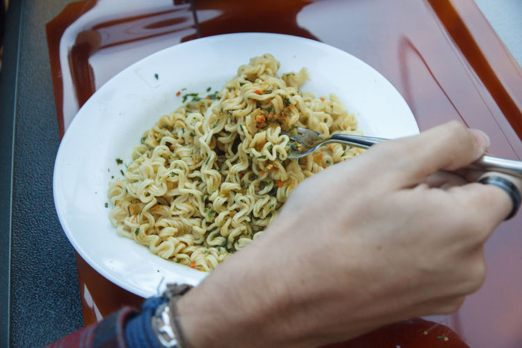 Cropped hand having noodles at table