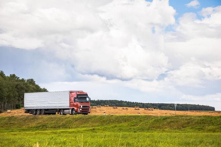 Truck on grassy field against sky