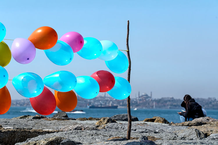 Multi colored balloons on rocks against blue sky
