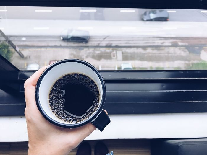EyeEm Selects Human Hand Drink Coffee - Drink Human Body Part Coffee Cup Refreshment One Person Food And Drink Holding Real People Close-up Personal Perspective Day Transportation Mode Of Transport Window Freshness Focus On Foreground Indoors  Land Vehicle Coffee Mug Morning