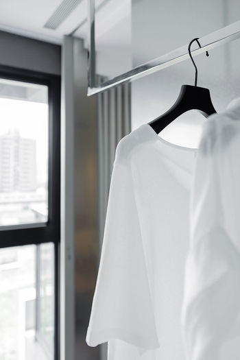 White shirt hanging Coathanger Indoors  Clothing Hanging Window No People White Color Day Close-up Store Fashion Furniture Clothes Rack Side View Focus On Foreground Shopping Garment Clean Pure Shirt T-shirt Simplicity Room Hanger Light