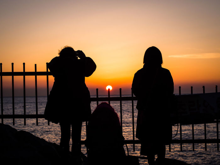 Silhouette people photographing sea against sky during sunset