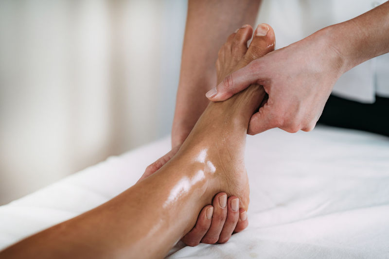 Midsection of massage therapist massaging female customer leg in spa