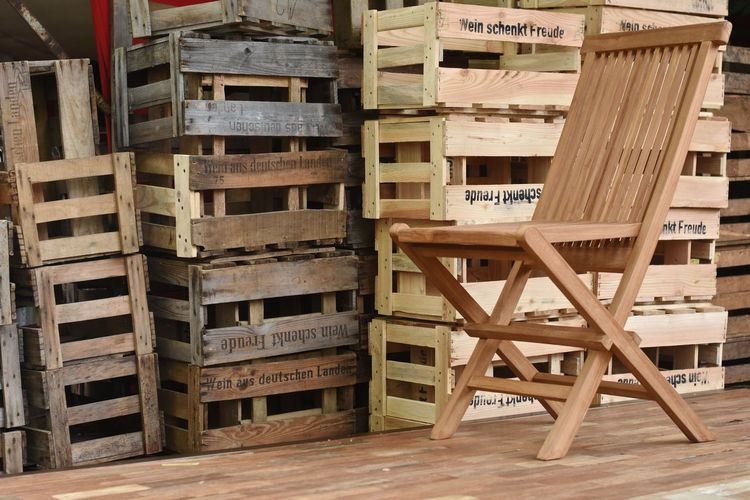 Stack Of Wooden Crate And Empty Chair In Warehouse