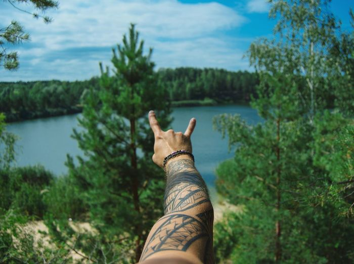 Cropped Hand Of Man With Tattoo Gesturing Against Lake
