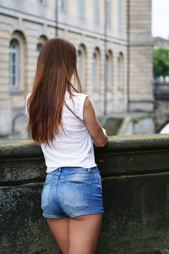 Rear view of woman standing against parapet