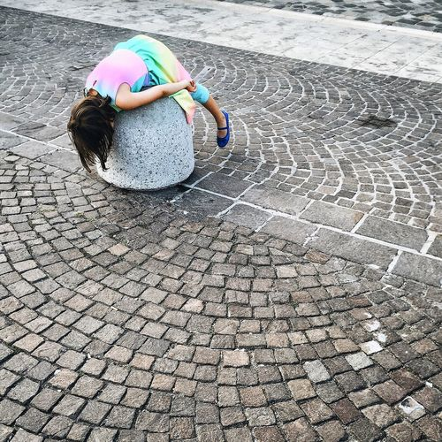 Rear view of boy on cobblestone