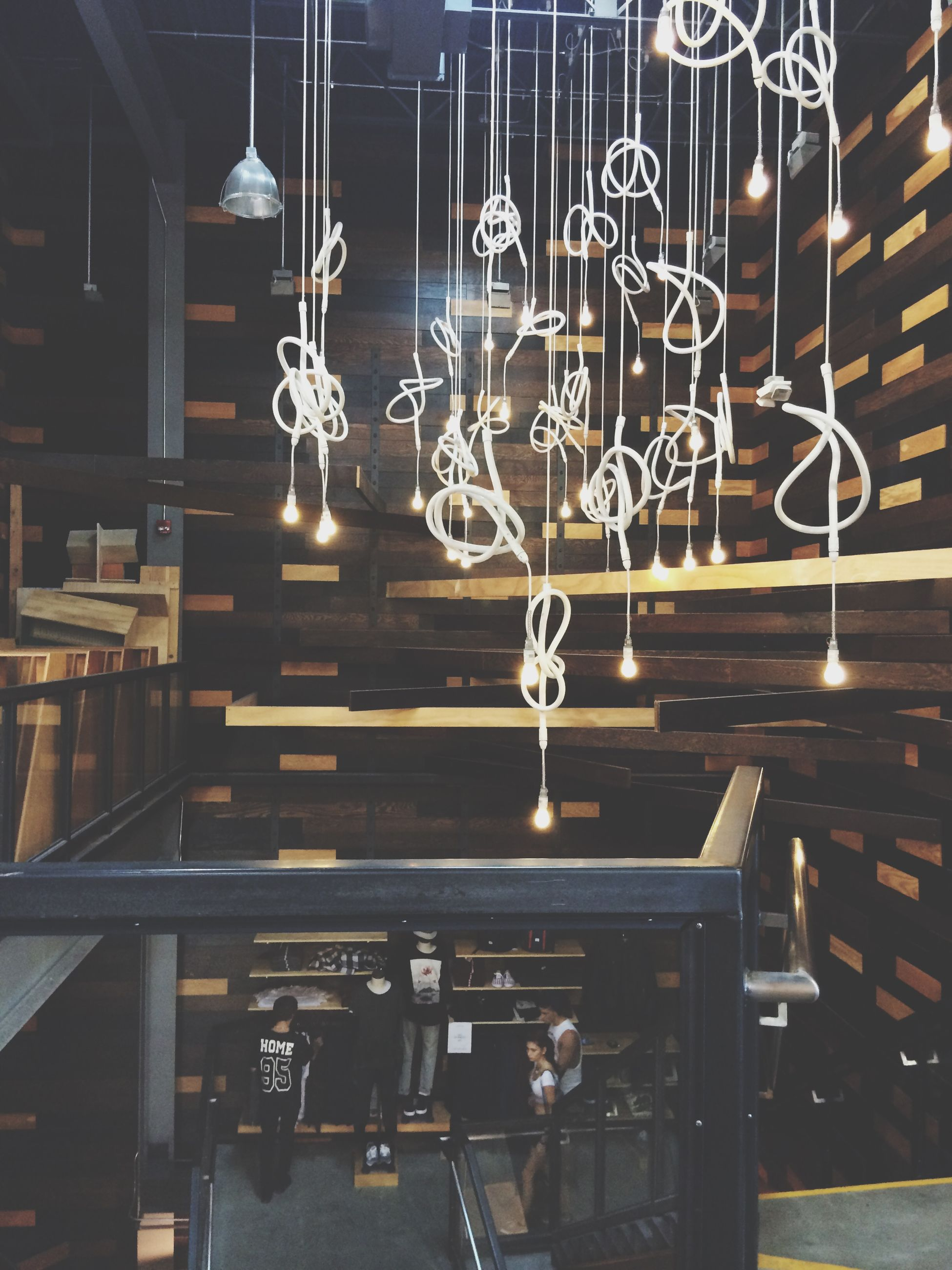 indoors, hanging, illuminated, lighting equipment, decoration, built structure, architecture, wall - building feature, window, low angle view, ceiling, no people, art and craft, electric lamp, glass - material, electric light, chair, table, in a row, store