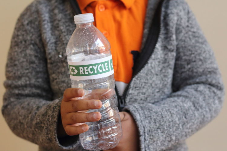 Midsection of person holding plastic bottle