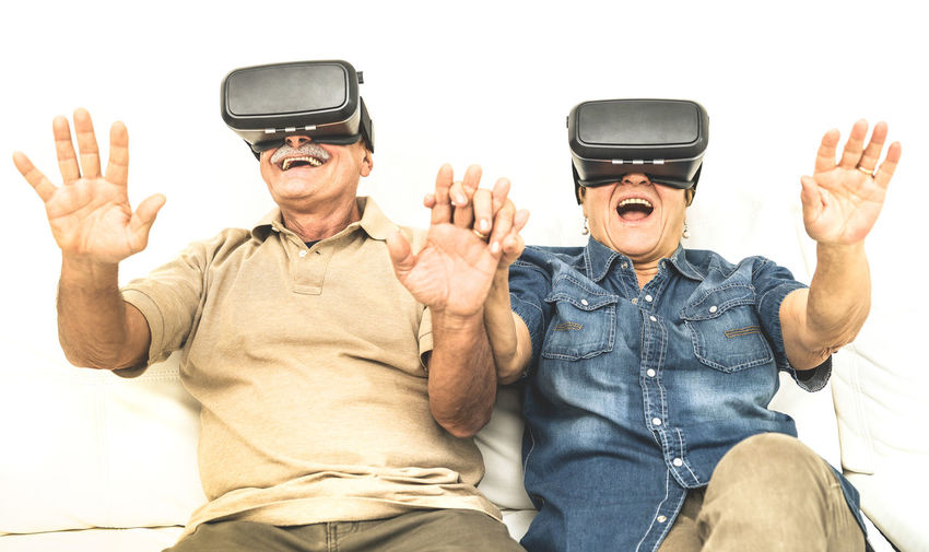 Happy Friends Wearing Virtual Reality Simulator At Home