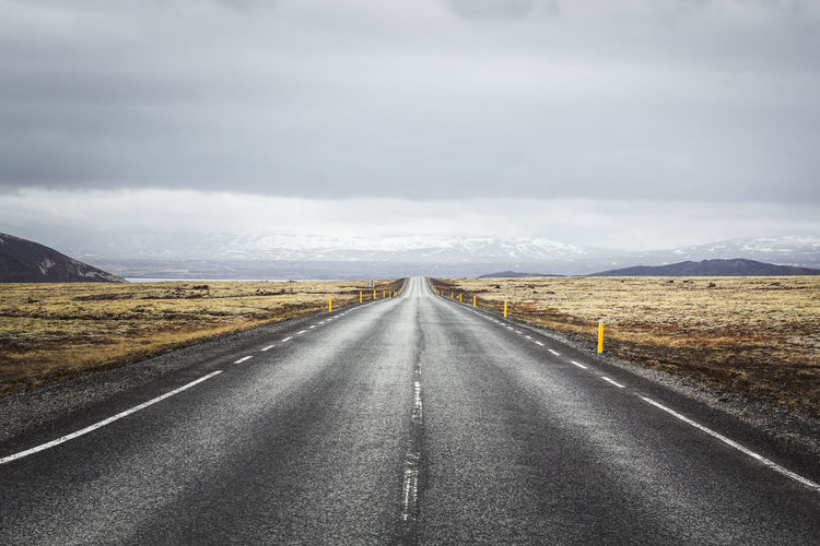 Empty road along countryside landscape against cloudy sky