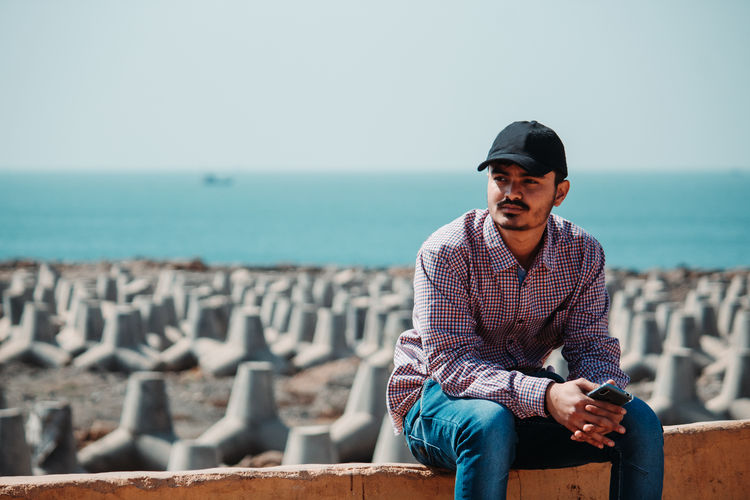 Man looking away while sitting against sea