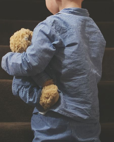 Rear view of boy holding teddy bear against staircase