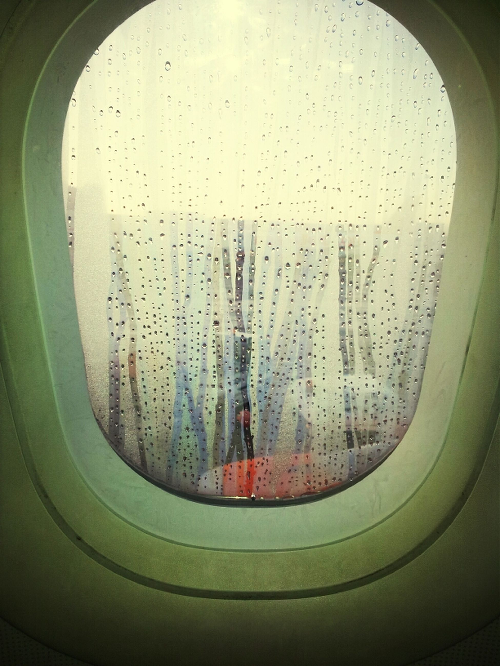 window, indoors, glass - material, transparent, airplane, vehicle interior, looking through window, transportation, air vehicle, mode of transport, glass, sky, built structure, architecture, travel, day, flying, no people, low angle view, part of
