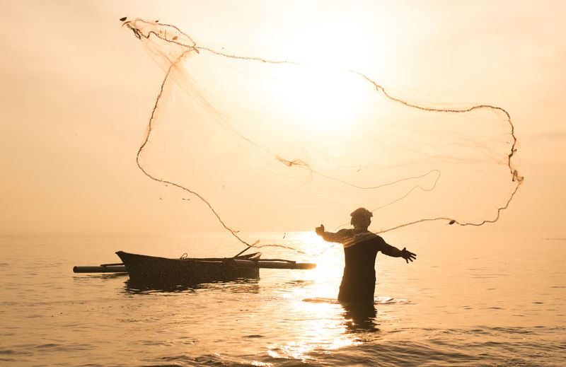 fisherman during sunrise. Water Nautical Vessel Fishing Net One Person Fishing Sky Sunset Fisherman Real People Sea Transportation Occupation Mode Of Transportation Men Nature Holding Standing Silhouette Lifestyles Fishing Industry Outdoors