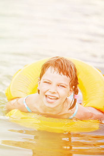 Portrait of smiling girl with inflatable ring in sea