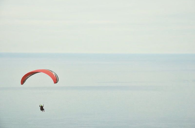 Person paragliding over seascape against sky