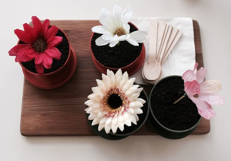 High angle view of artificial flowers in cakes on wooden tray