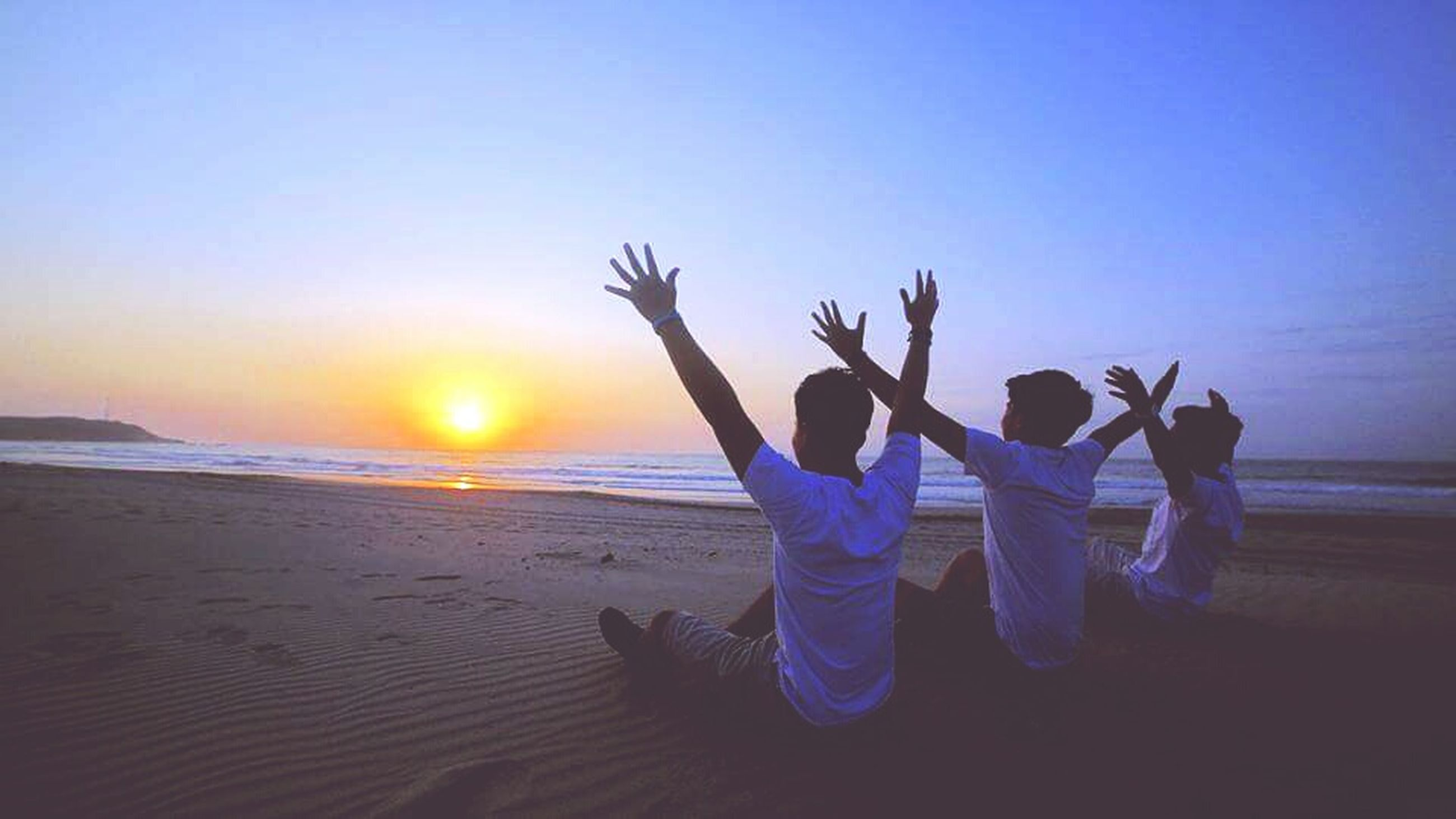 beach, sand, sea, sunset, real people, arms raised, lifestyles, leisure activity, enjoyment, nature, water, men, sky, beauty in nature, togetherness, outdoors, women, horizon over water, night, people, adult