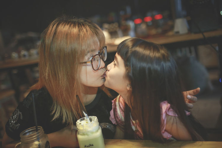 Mother Kissing Daughter While Sitting At Cafe