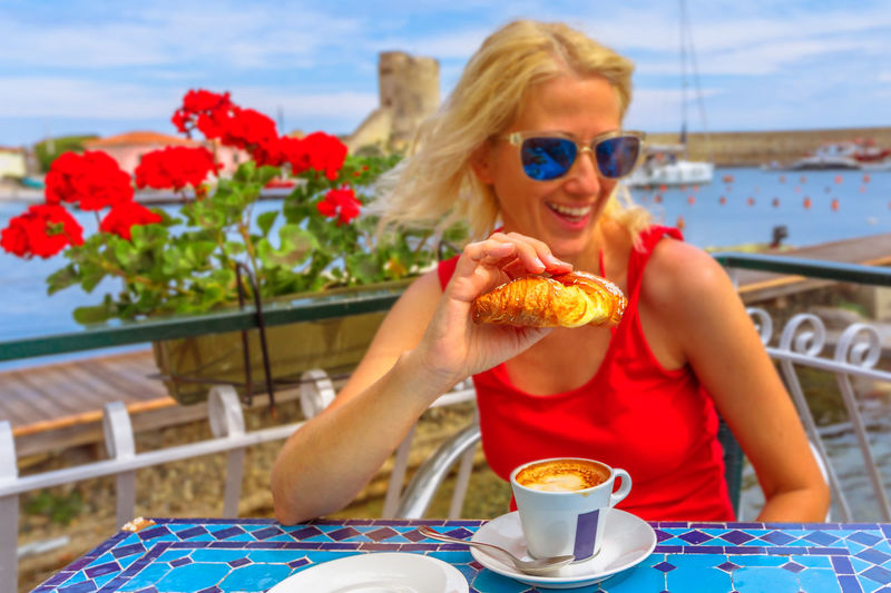 Smiling woman wearing sunglasses eating food sitting at cafe
